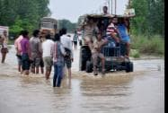 People at a road in a locality flooded by Ramganga River in Moradabad district