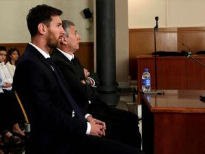 Barcelona's Lionel Messi, foreground, and his father Jorge Horacio Messi sit in court in Barcelona, Spain