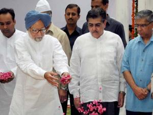 Former Prime Minister Manmohan Singh with former president Fakhruddin Ali Ahmed's sons  Pervez Ahmed (2nd R) and Justice Badar Durrez Ahmed (R) paying floral tribute at his 'Mazar' on his death annive