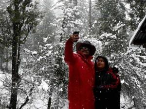 A tourist couple takes selfie with his mobile during fresh snowfall at Tangmarg in Baramulla District of North Kashmir