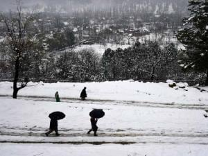 People walk with umbrellas during fresh snowfall at Tangmarg in Baramulla District of North Kashmir