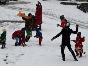 Tourists with their children enjoy snow balls during fresh snowfall at Tangmarg in Baramulla District
