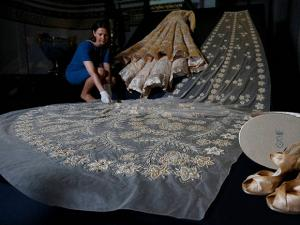 A woman adjusts Britain's Queen Elizabeth  wedding dress at an exhibition at Buckingham Palace