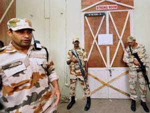 Security officers guard  GCT College in Coimbatore where sealed electronic voting machines are kept after assembly elections