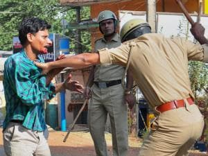 Police beating up one of the garment workers who were protesting over EPF withdrawal norm, in Bengaluru