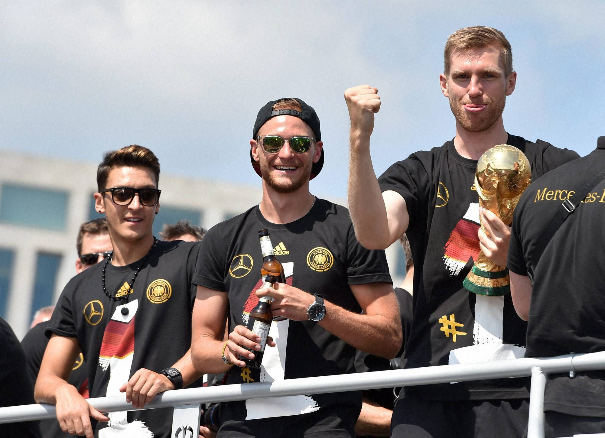 German national soccer players, Mesut Özil, Benedikt Hoewedes, Per Mertesacker, celebrate, tour Berlin, bus,   Germany's World Cup-winning team, returned, home, Brazil, celebrate, country's, fourth title, huge crowds, fans, team's Boeing, 747 touched down, Berlin's Tegel, airport , midmorning, fan mile, Brandenburg Gate