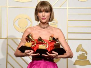 Taylor Swift poses in the press room with the awards for album of the year for 1989