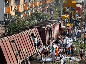 People unload cargo from a goods train that derailed on the harbour line near Guru Tegh Bahudur station in Mumbai