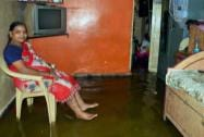 A woman at her residence flooded after heavy rain in Mumbai