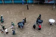 People wade through a water logged road after heavy rains near Elphinstone in Mumbai