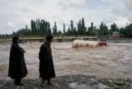 Local people look at an oil tanker stranded in middle of a river after heavy rainfall caused floods in Anantnag