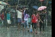 People cross a road in heavy rains in Kolkata