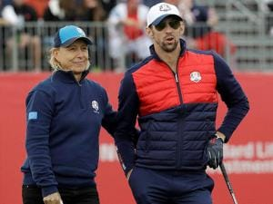 Michael Phelps and Europe's Martina Navratilova wait to tee off