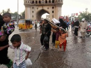 People walk on a water logged street near Hyderabad's Chaar Minar after heavy rains in the city