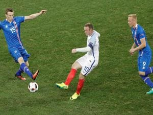 England's Wayne Rooney, cent, is challenged by Jon Dadi Bodvarsson, left, and Kolbeinn Sigthorsson, during the Euro 2016