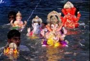Devotees immerse idols of Ganesha into a lake in Thane