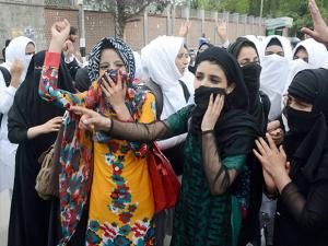 College girls shout slogans at a protest against the recent police action on students, in Srinagar