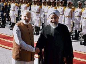 Prime Minister Narender Modi shakes hands with Iranian President Hassan Rouhani, after reviewing guard of honour at the Saadabad Palace in Tehran