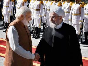 Prime Minister Narender Modi shakes hands with Iranian President Hassan Rouhani, after reviewing guard of honour at the Saadabad Palace in Tehran, Iran
