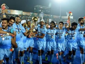 Indian Junior hockey players celebrate with the winning trophy after their victory over Belgium