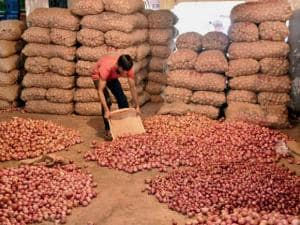 A Vendor sorts onions in his shop at Sardar Vegetable Market in Surat