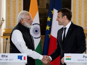 French President Emmanuel Macron and Indian Prime Minister Narendra Modi shake hands