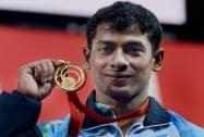 Gold medal winner India's Sukhen Dey celebrates after the men's 56 kg weightlifting