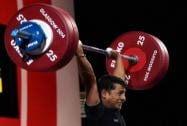 India's Sukhen Dey completes a lift during the 56-kg men's weightlifting