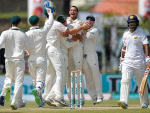 Mitchell Starc, center, celebrates with team mates after taking the wicket of Sri Lanka