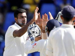 India's Ravichandran Ashwin, left, is congratulated by teammates after dismissing West Indies' Devendra Bishoo