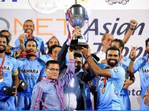 Indian hockey players pose with the Asian Champions Trophy after they beat Pakistan