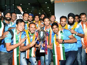 Sardar Singh  pose with the Asian Champions Trophy as they arrives at  T3 terminal in New Delhi