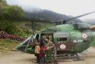 Army personnel help a woman in getting off a chopper during their rescue operation in earthquake-hit Nepal