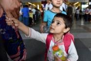 A child holds finger of his family member after evacuated from earthquake hit Nepal arrive at IGI airport T3 in New Delhi