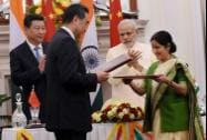 Prime Minister Narendra Modi and Chinese President Xi Jinping clap as External Affairs Minister Sushma Swaraj and her Chinese counterpart Wang Yi exchange files