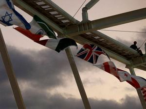 A worker hangs flags from the roof of the Olympic Tennis Center a preparations continue for the 2016 Summer Olympics