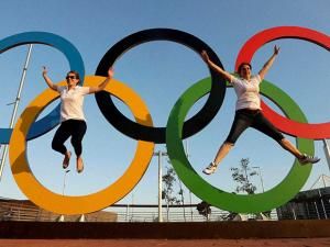 Emily Bevan, left, and Victoria Fecci, pose for a photo with the Olympic Rings at the Olympic Park