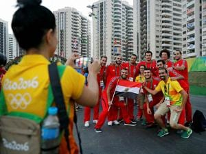 Members of the Egyptian Olympic delegation pose for a photo with volunteers in athletes village