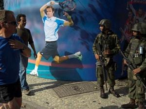 Soldiers stand in guard next to a wall decorated with a banner featuring Russian tennis player Teymuraz Gabashvili