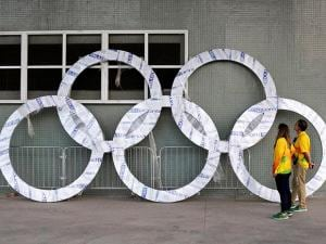 Workers inspect a set of Olympic Rings that are scheduled to be installed inside Olympic Park