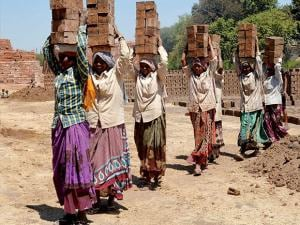 Women laborers carry bricks on their heads at a brick factory on the eve of International Women's Day in Karad, Maharashtra