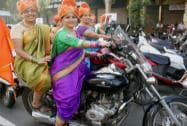 Women dressed in traditional attire take part in a bike rally on the occasion of International Women's Day