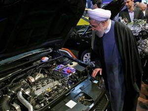 President Hassan Rouhani looks at the engine of a car while visiting the International Car Industry Show in Tehran, Iran
