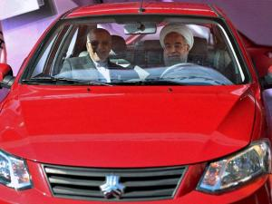 President Hassan Rouhani, right, unveils the Saina domestically built car while visiting the International Car Industry Show