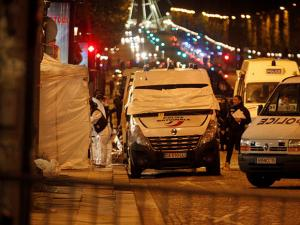 Forensic experts and police officers examine evidence from a police van on the Champs Elysees in Paris