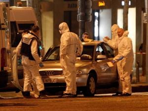 Forensic experts collect evidences from the car belonging to an attacker who killed a police officer