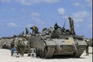 Israeli soldiers stand near tanks at the Israel-Gaza border