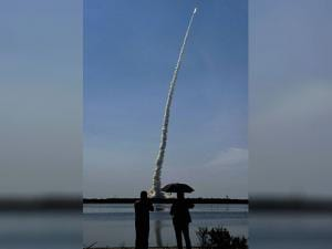 Onlookers look at PSLV C-34 rocket disappearing  into sky after being launched