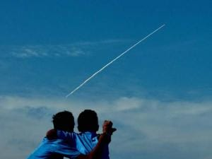 Two boys enjoy the sight ISRO's PSLV-C32 leaving a trail of smoke after it was launched, at the Marina in Chennai on Thursday. It was launched from Sriharikota