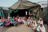 Flood hit people near tent at a relief camp at Sure Chak village in Jammu